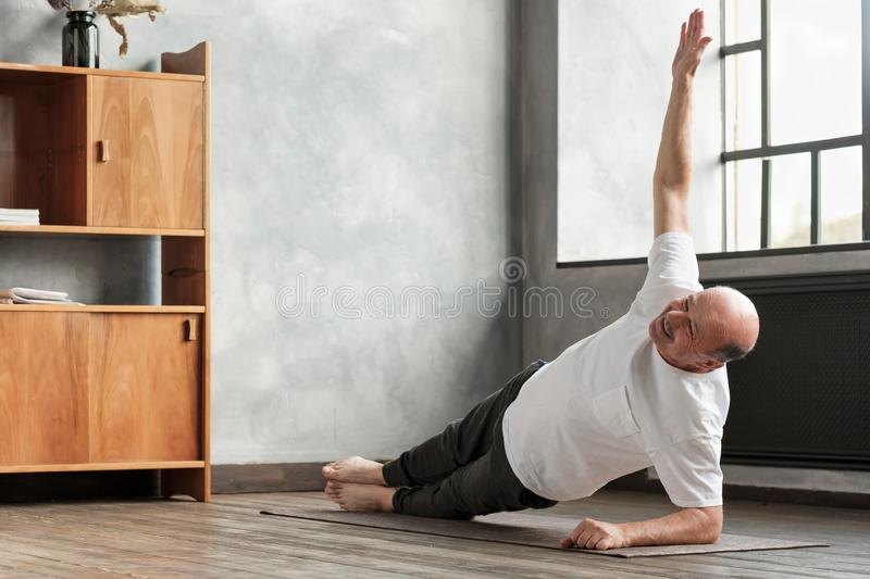 Man doing a side plank exercise at living room. stock photography