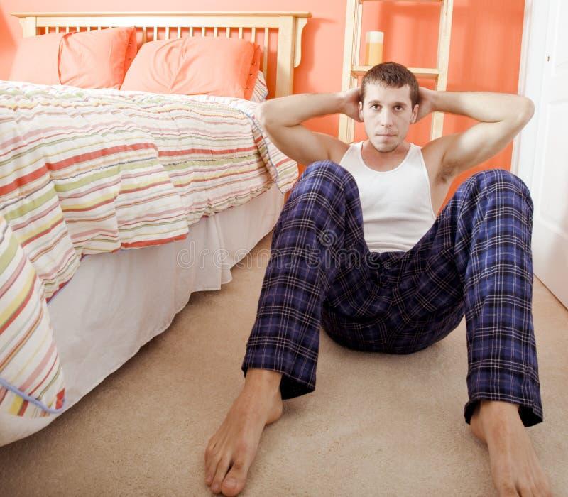 Man Doing Sit-Ups In Bedroom Stock Photo