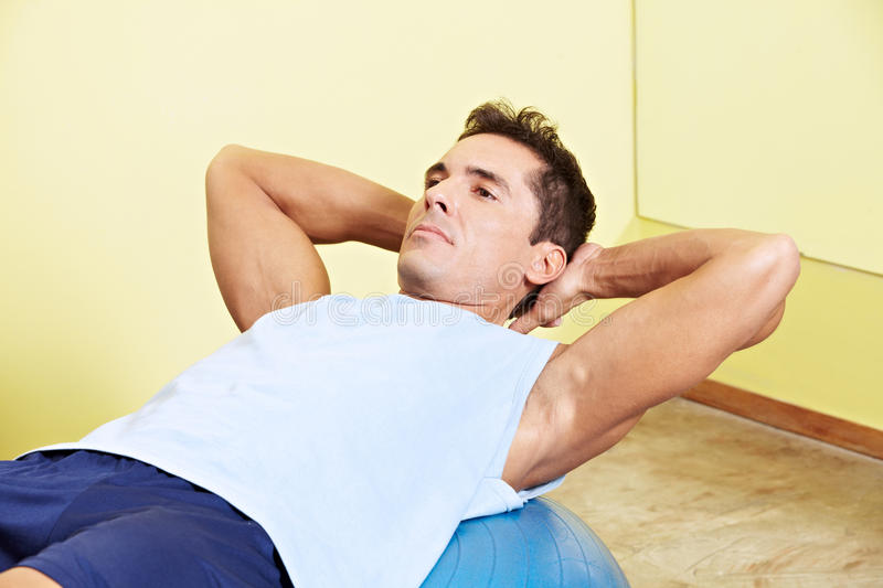 Man doing sit-ups in gym. Man doing sit-ups in fitness center on gym ball royalty free stock photo