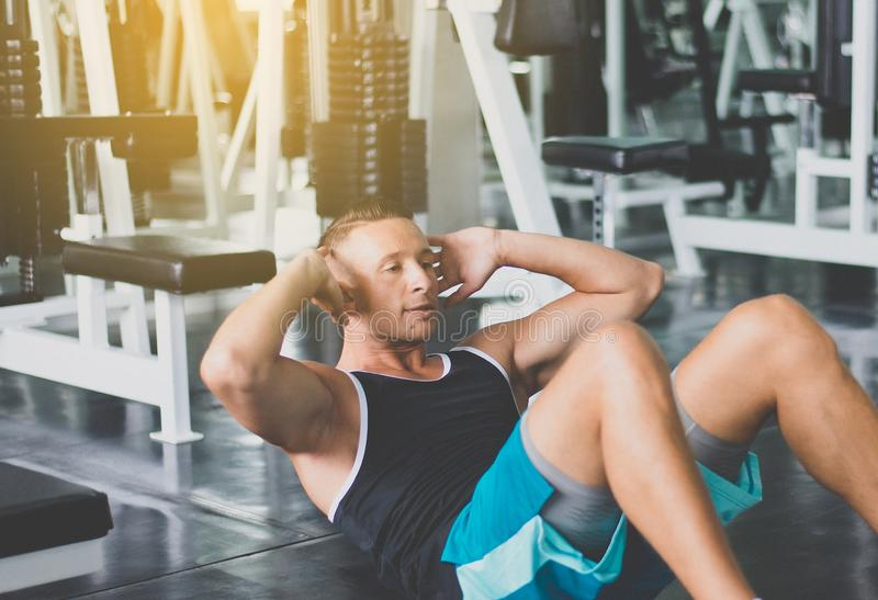 Man doing situp or crunches in gym,Men exercise muscular his stomach in door. Male doing situp or crunches in gym,Men exercise muscular his stomach in door stock photos