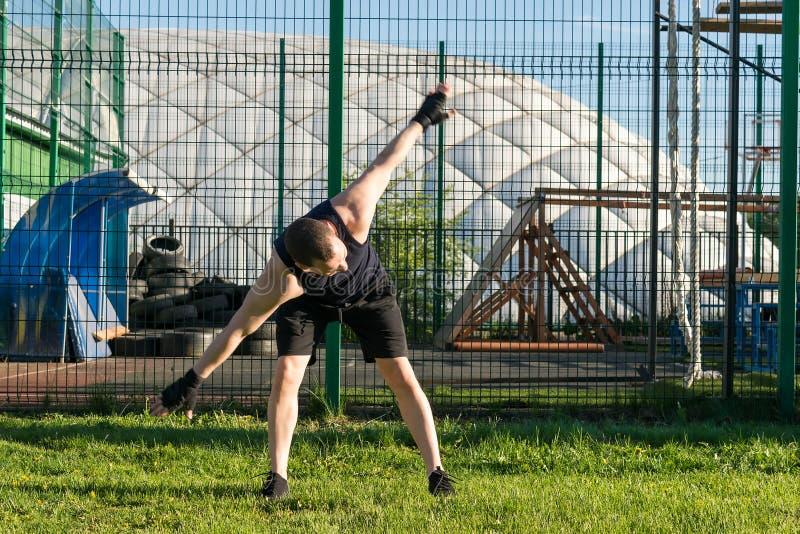 Man doing sport exercises outdoors on green grass stock photos