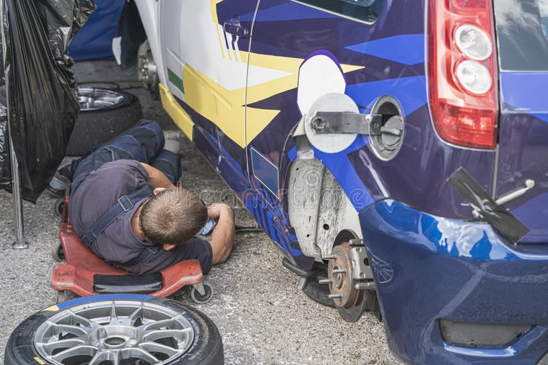 Man is doing sports car maintenance, the car is broken and without wheels. Mechanic lying near automobile and repair vehicle stock photo