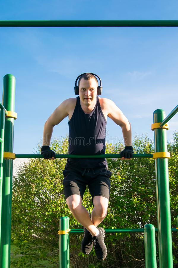 Man doing sports, outdoors, doing push-UPS on the bar, listening to music, against the sky stock photo