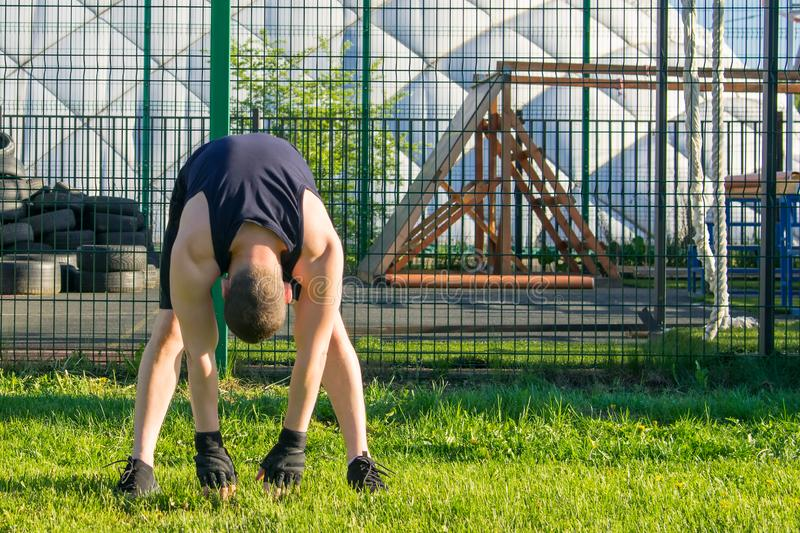 Man doing sports outdoors stretching his back royalty free stock photos