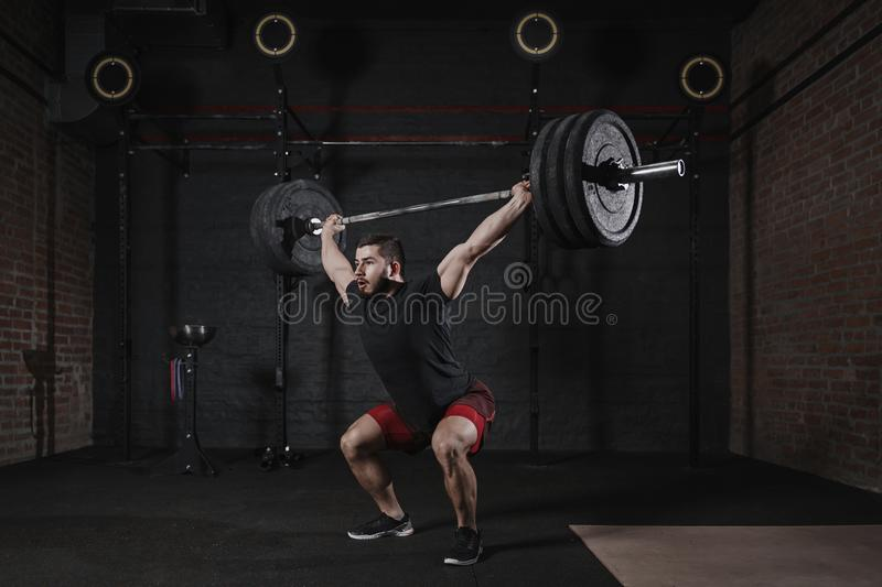 Man doing squats with heavy barbell overhead at gym. Handsome man practicing functional training powerlifting exercises royalty free stock photo
