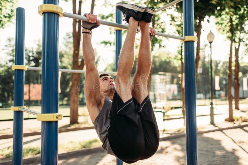 Man doing stretching exercise using horizontal bar stock images