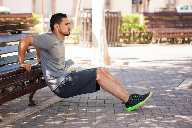 Man doing tricep dips in a park bench. Profile view of a strong man exercising his arms and doing tricep dips outdoors in a park bench stock image