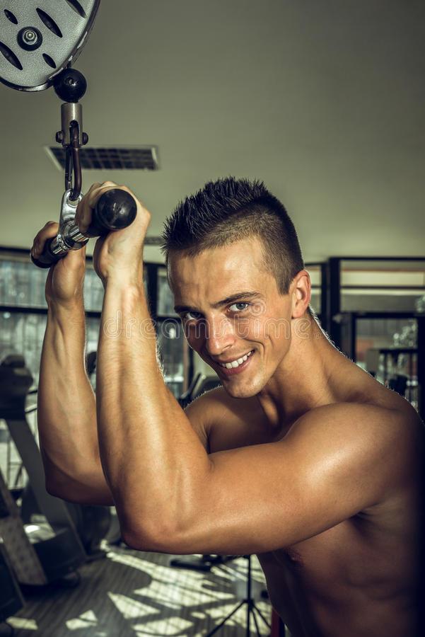 Man doing triceps pull downs royalty free stock image
