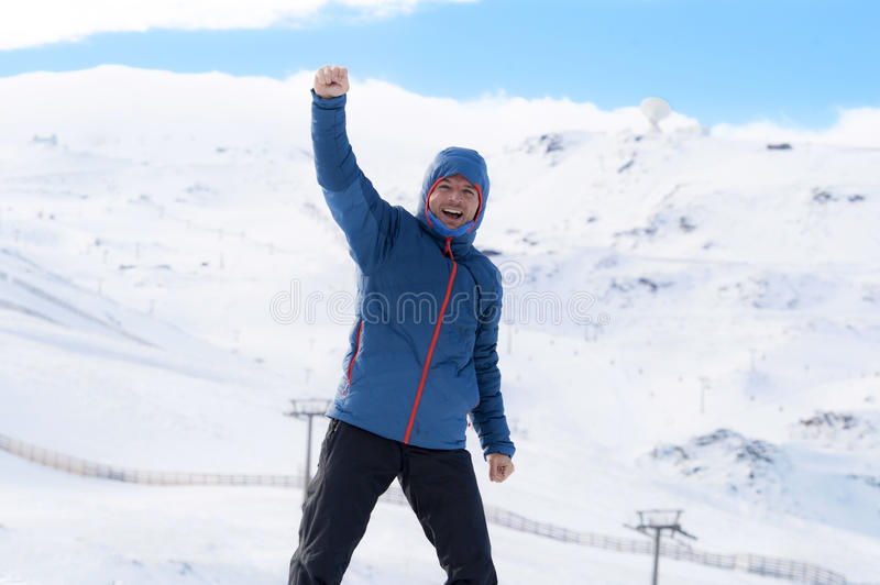 Man doing victory sign after peak summit trekking achievement in snow mountain on winter landscape stock photo