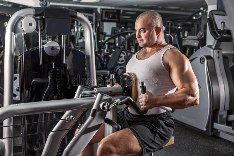 Man doing workout with pull-down machine stock image
