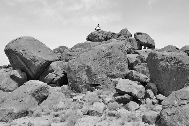 Man doing yoga concentration on a pile of rocks #3 -B&W-. Man in deep reflexion on a pile of rocks in the desert royalty free stock image