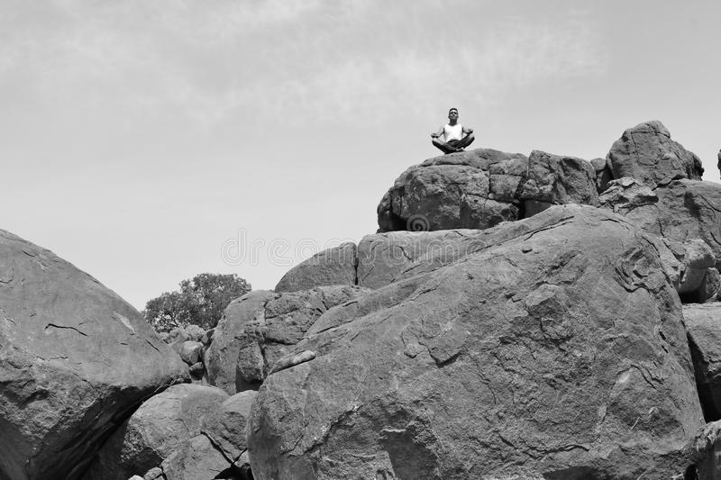 Man doing yoga concentration on a pile of rocks #2 -B&W-. Man in deep reflexion on a pile of rocks in the desert royalty free stock photos