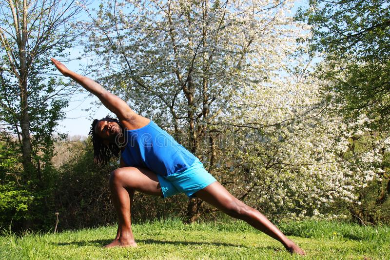 A man doing a Yoga exercise outdoors royalty free stock image