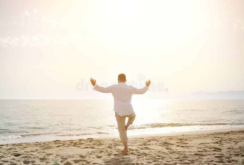 Man doing yoga exercises on the beach - healthy lifestyle concept. Man doing yoga meditation exercises on the beach at sunset- healthy lifestyle concept royalty free stock image