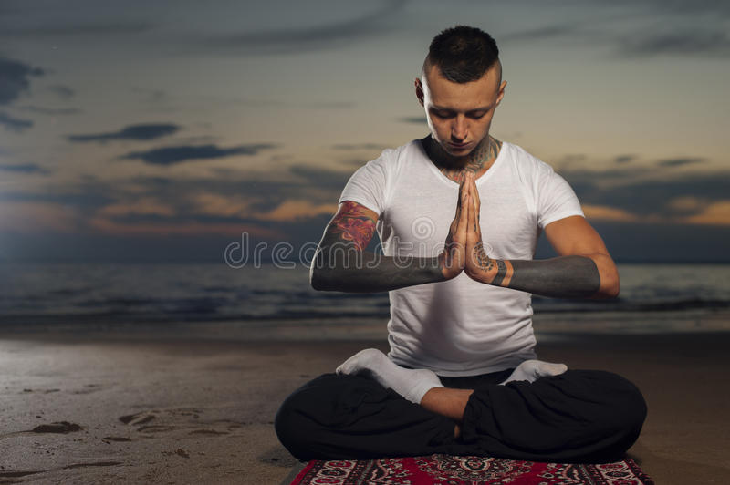 Man doing yoga and meditating in lotus pose stock images
