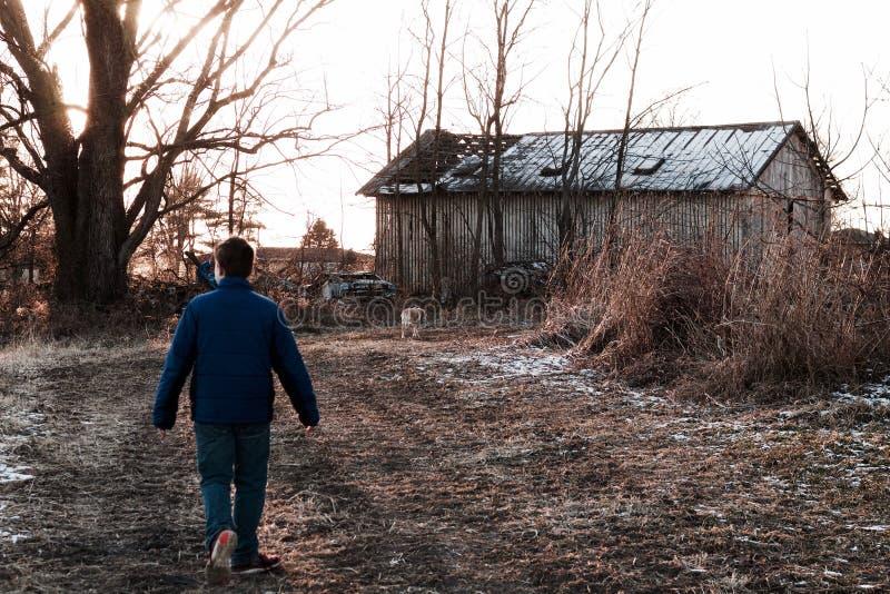 Man draagt een blauwe jas dicht bij een bladloze boom stock afbeeldingen
