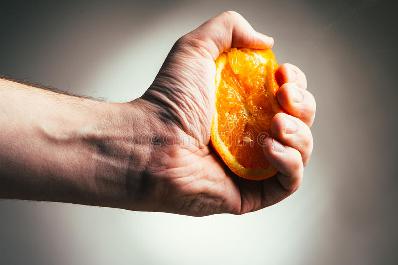 Man dramatic squeezes orange. Conceptis tired from work. stock photo
