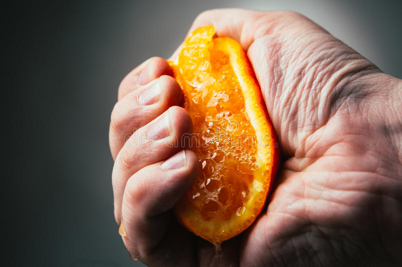 Man dramatic squeezes orange. Conceptis tired from work. royalty free stock photos