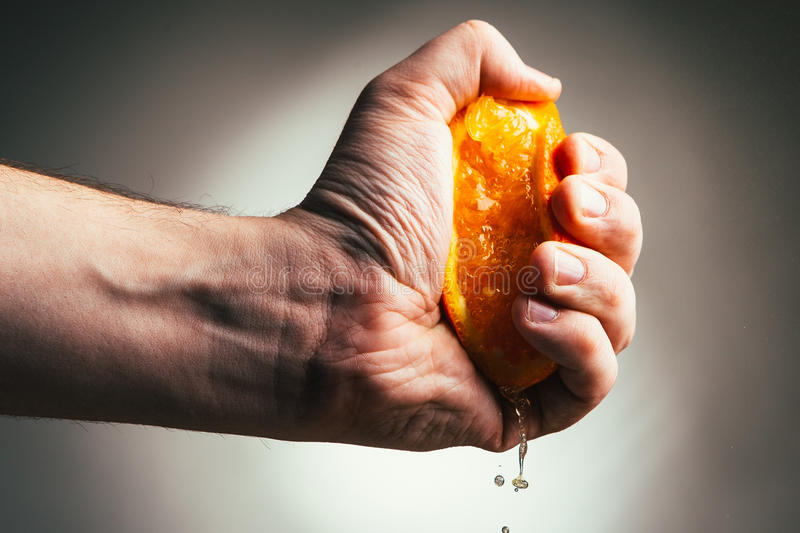 Man dramatic squeezes orange. Conceptis tired from work. stock photography