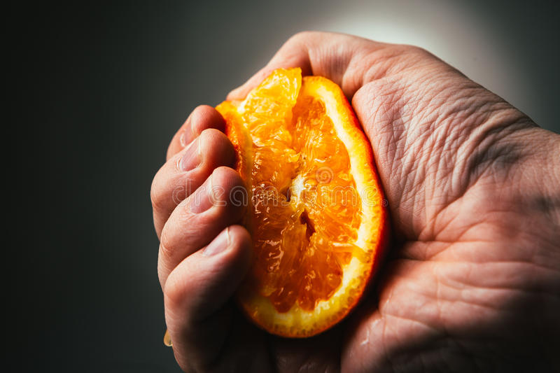 Man dramatic squeezes orange. Conceptis tired from work. royalty free stock photography