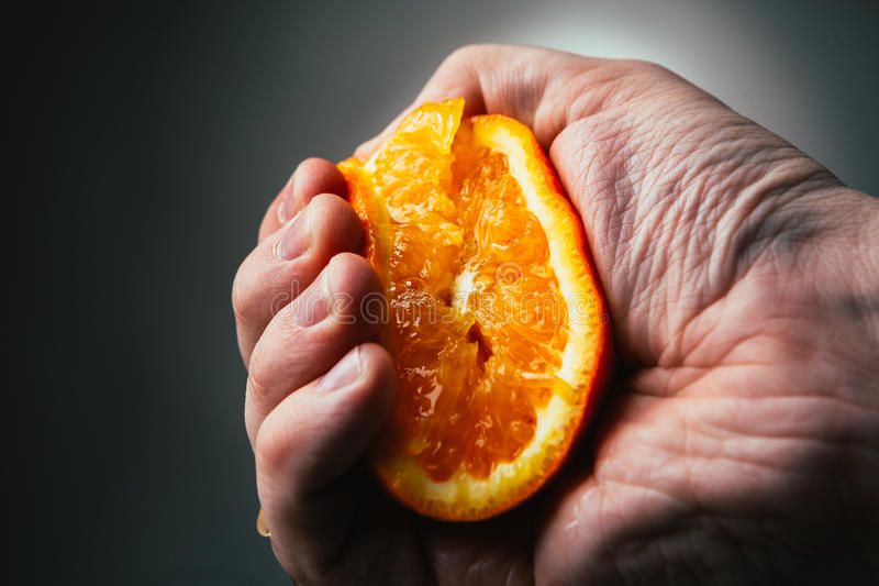 Man dramatic squeezes orange. Conceptis tired from work. royalty free stock images