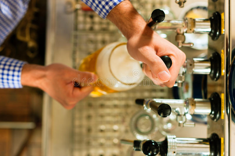 Man drawing beer from tap stock photos