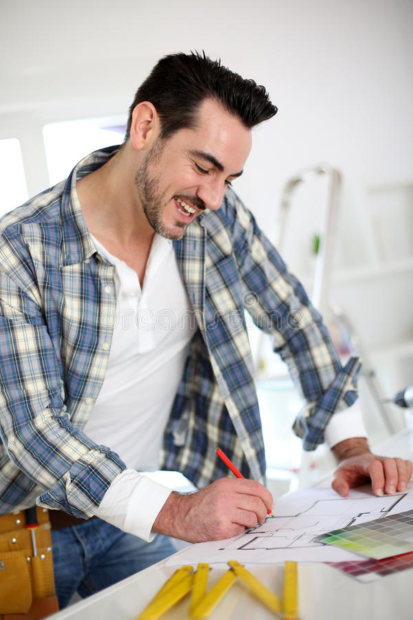 Man drawing blueprint before beginning works royalty free stock photography