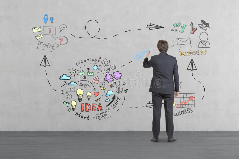 Man drawing business idea sketch on concrete wall royalty free stock photography