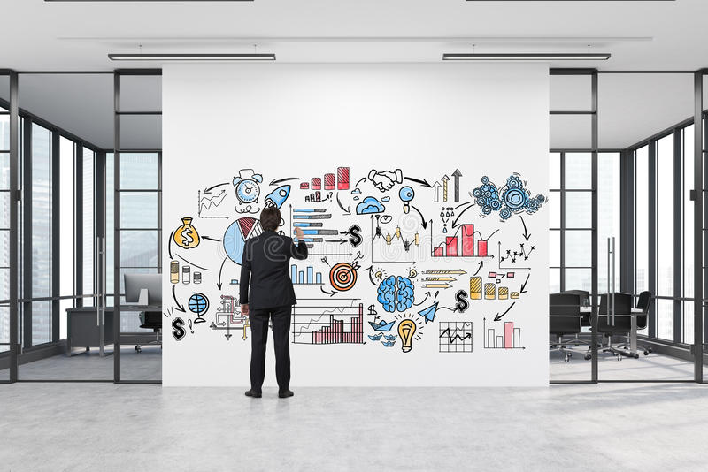 Man drawing a business poster in a corridor with two meeting rooms. Rear view of a man drawing a business poster on a large white wall with two conference rooms stock photography