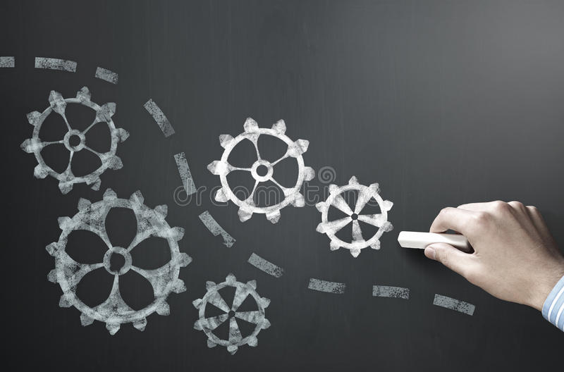 Man drawing gears on blackboard. Businessman hand drawing with chalk gears mechanism as teamwork concept stock image
