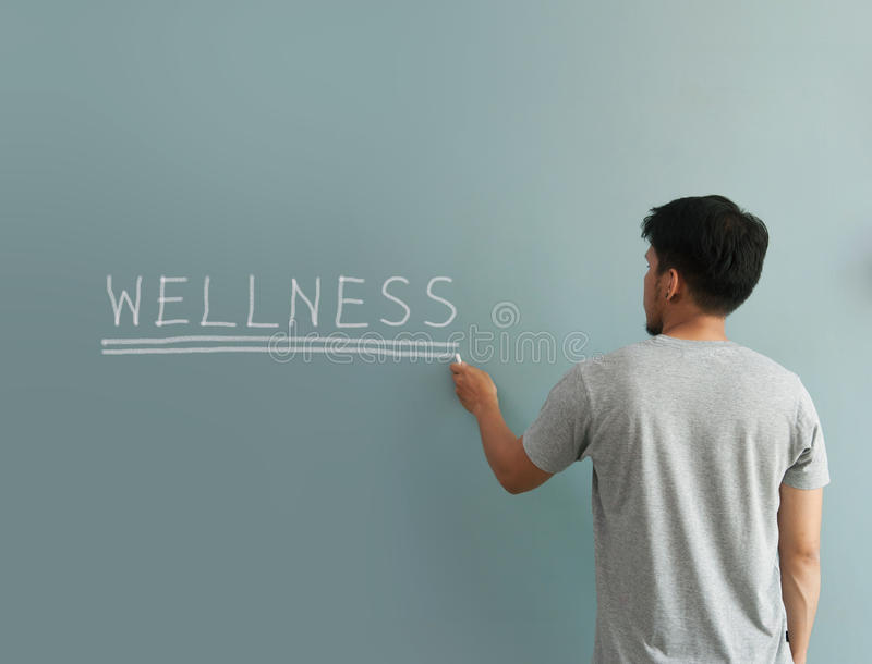 Man drawing heart for valentines day with white chalk on wall. royalty free stock photo