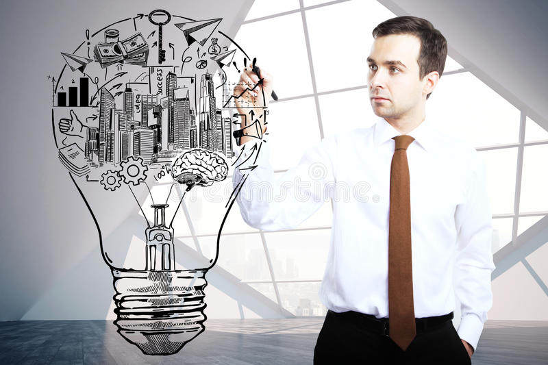Man drawing lamp with business icons stock photos