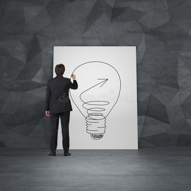 Man drawing lamp on poster. Businessman drawing lamp on poster stock image