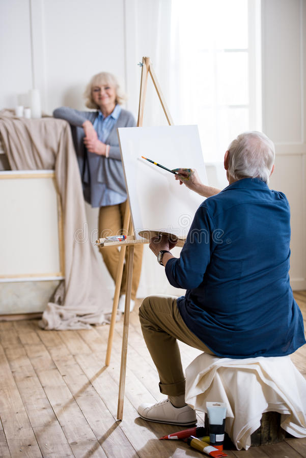 Man drawing portrait of smiling woman in art workshop royalty free stock photos