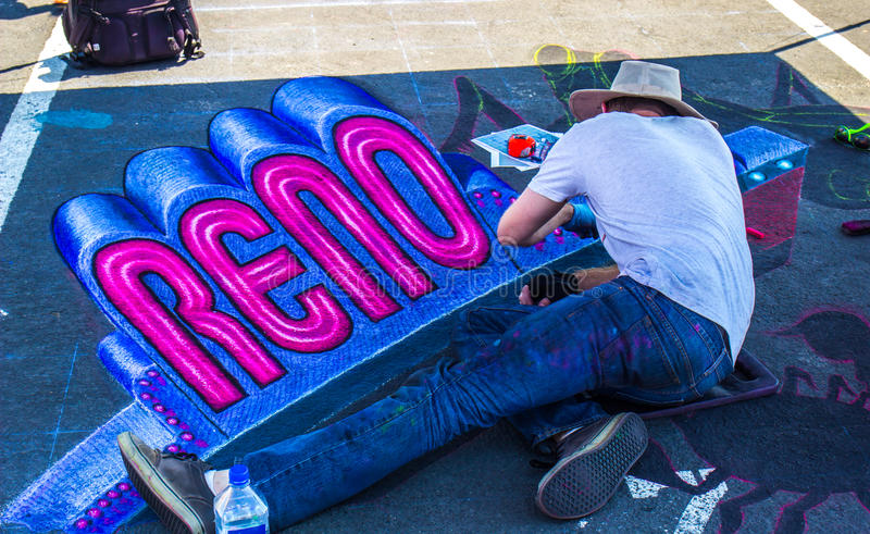 Man Drawing Reno Sign On Chalk The Walk royalty free stock photography