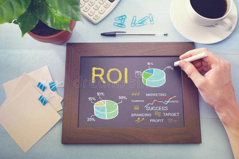Man drawing ROI concept on chalkboard. (return on investment stock images