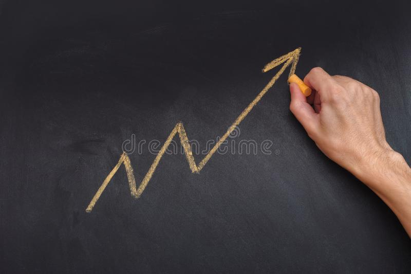 Man drawing yellow arrow showing upward trend and increasing pro. Fits on blackboard. Close up stock images