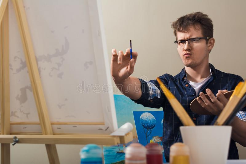 The man draws a picture. The man nursed drawing. The artist draws a picture stock photography