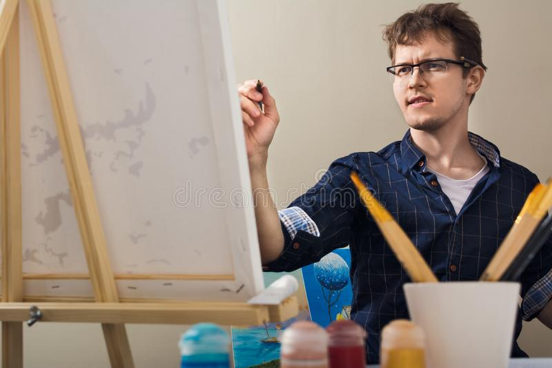The man draws a picture. The man nursed drawing. The artist draws a picture royalty free stock image