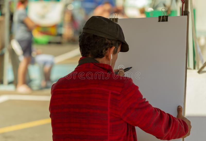 Man draws the portrait on white paper at the street.  stock photo