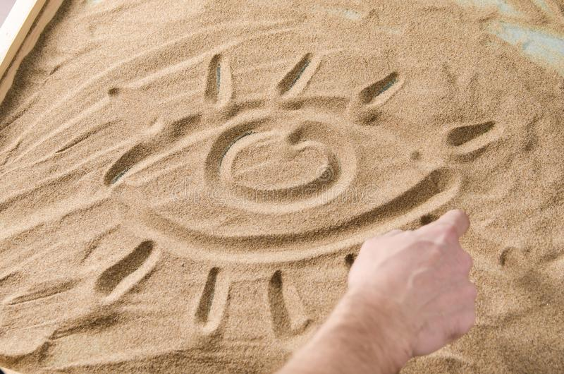 A man draws on the sand symbol of eye. A man draws by his finger on the sand symbol of eye royalty free stock image