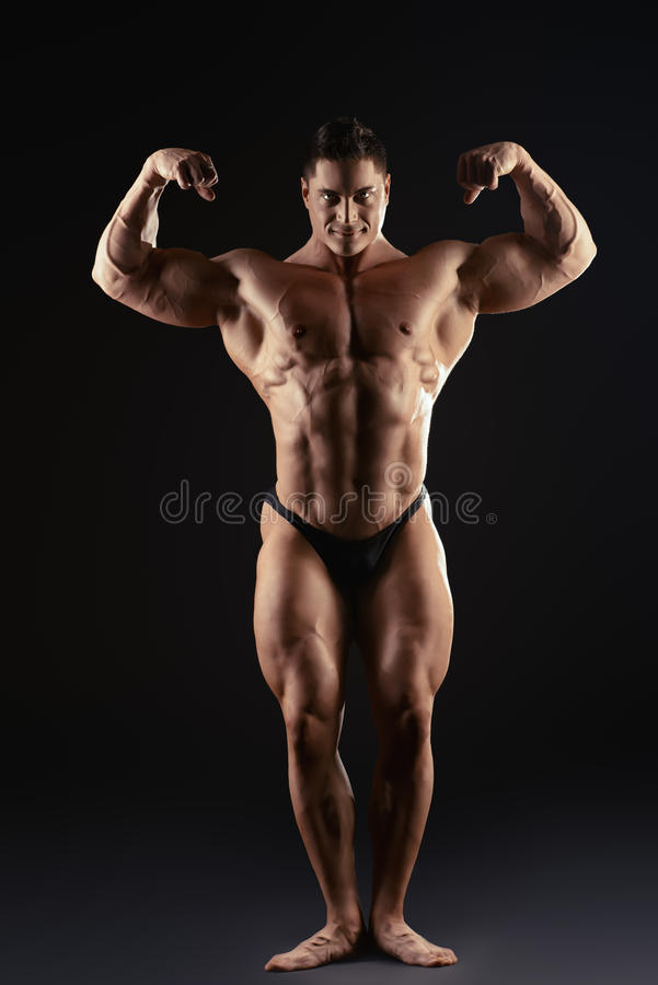 Man dream. Full length portrait of a handsome muscular bodybuilder posing over black background royalty free stock photography