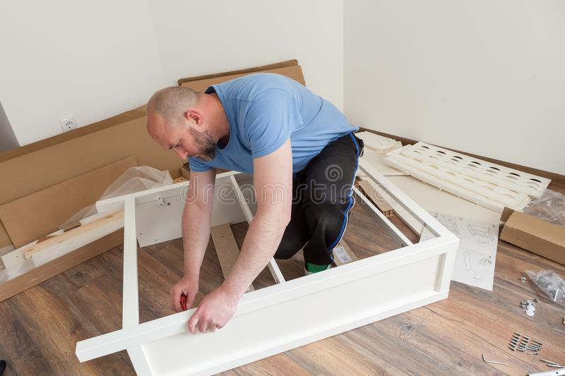 Man dressed casual assembling furniture in new house. Carpenter repair and assembling furniture at home royalty free stock image