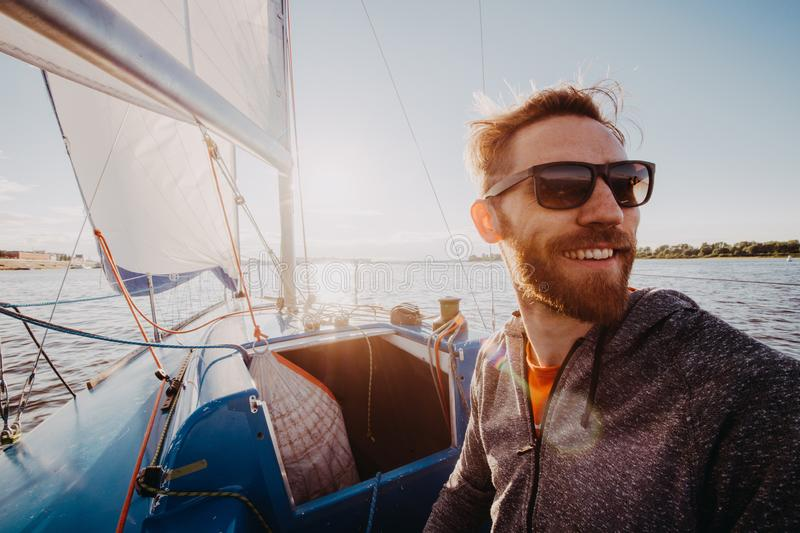 Man dressed in casual wear and sunglasses on a yacht. Happy adult bearded yachtsman close-up portrait. Handsome sailor royalty free stock photo