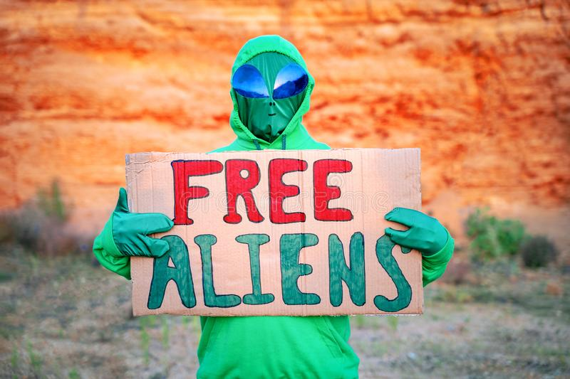 A man dressed in a green alien carnival costume suit at a lone rally with a sign `free aliens` on the background of a desert can. Yon royalty free stock photo