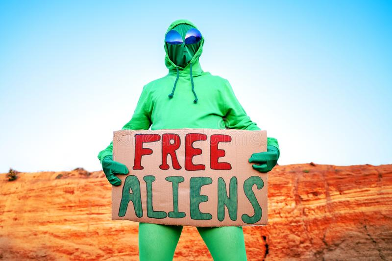 A man dressed in a green alien carnival costume suit at a lone rally with a sign `free aliens` on the background of a desert can. Yon stock images
