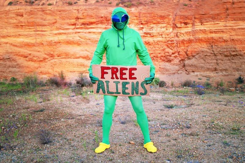 A man dressed in a green alien carnival costume suit at a lone rally with a sign `free aliens` on the background of a desert can. Yon stock image