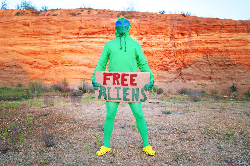 A man dressed in a green alien carnival costume suit at a lone rally with a sign `free aliens` on the background of a desert can. Yon stock photo