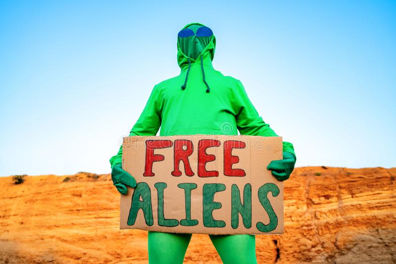 A man dressed in a green alien carnival costume suit at a lone rally with a sign `free aliens` on the background of a desert can. Yon royalty free stock images