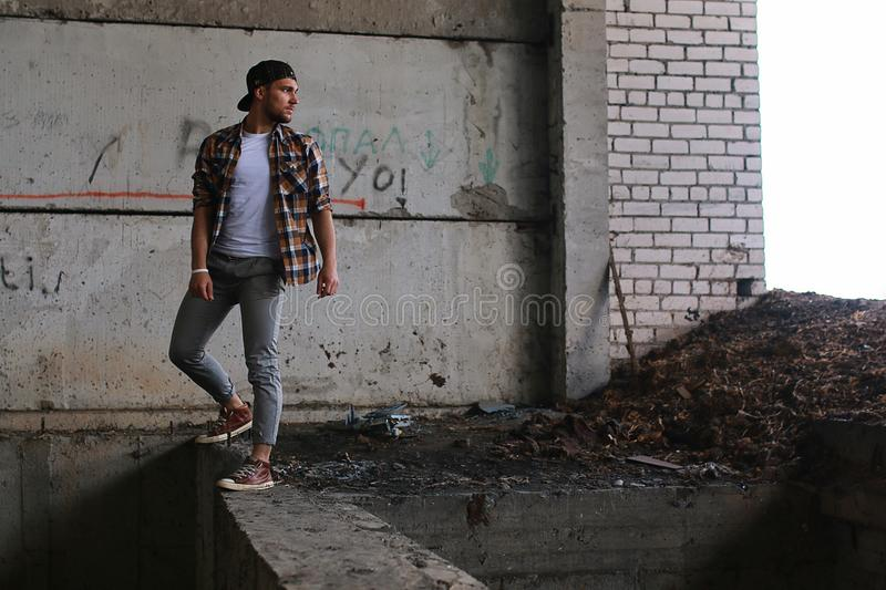 A man dressed in hip hop style poses. On camerar stock image